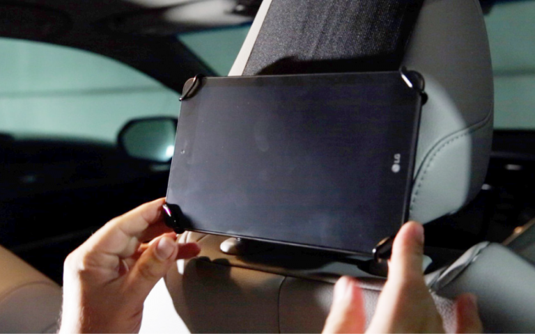 Insert tablet towards bottom of headrest with charge port on right